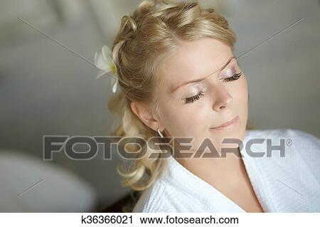 Stock photography of beautiful cute blond bride doing makeup before beautiful cute blond bride doing makeup before wedding day long lashes white flowers in hair smilling and happy perfect wedding preparation mightylinksfo