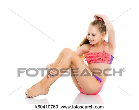 6101b94a3f3f A beautiful little school girl in a bathing suit is sitting on the studio  floor on a white background. The concept is suitable for illustrating  summer ...