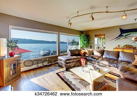 Luxus, wohnzimmer, mit, groß, leder, zerlegbar, couch, sitte, lichter, und,  zwei, groß, windows, mit, wasser, ansicht. Stock Bild