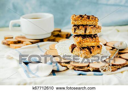 Organic homemade granola bars with salt date caramel and chocolate on blue background.Selective focus.A cup of coffee. Healthy breakfast.