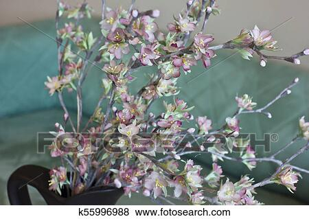 Cherry blossom pink artificial flowers made of silk on turquoise background