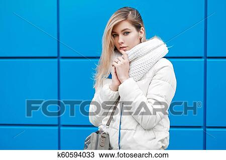 85ef804ec8f3a Beautiful young woman with fashionable knitted scarf and white winter jacket  with a bag near blue wall on a winter day