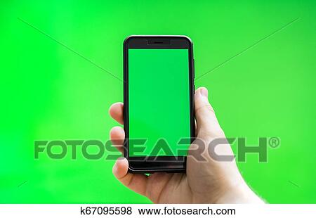 Male hand with Smartphone over green screen  Place for your advertisement   Stock Photo