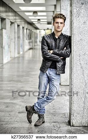 Picture Of Young Man With Leather Jacket Standing Outside Against