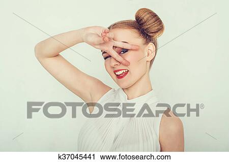 Beautiful girl with funny hairstyle makes peace sign hands, smiling and showing tongue.
