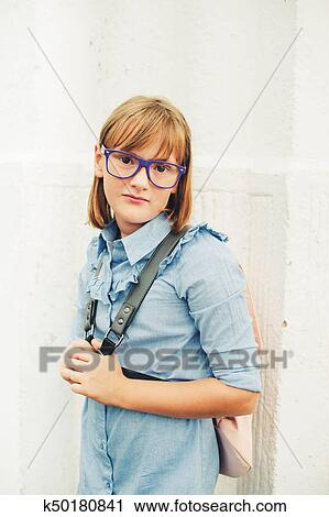 Outdoor Portrait Of A Cute Little 9 10 Year Old Girl Wearing Blue Uniform Dress Backpack And Glasses Back To School Concept Stock Image K50180841 Fotosearch