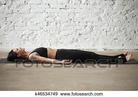 young yogi attractive woman in savasana pose white loft