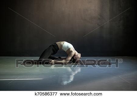 woman practicing yoga doing pigeon exercise kapotasana