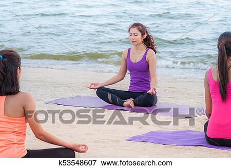 yoga class at sea beach in evening sunset group of asia