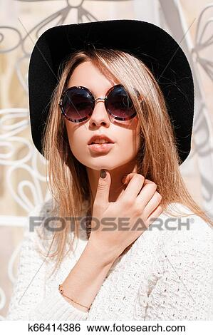 b35b8c9bc35 Portrait of an attractive young hipster woman in an elegant black hat in a  vintage knitted white sweater in round sunglasses with a necklace on a  white ...