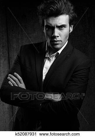 a4d1e910 Charismatic business handsome male with folded arms in blue fashion suit  and white style shirt looking on dark shadow background. Black and white  portrait