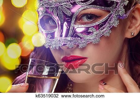 4b4b0331558e Beauty model woman wearing venetian masquerade carnival mask at party over  holiday dark background with magic glow. Christmas and New Year celebration.