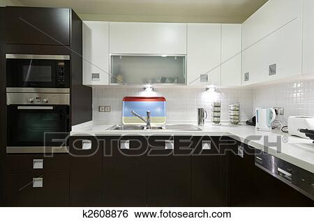 A Modern Kitchen With Sleek Brown Cabinets And Beautiful White Countertop Complete Stainless Steel Dishwasher Oven Microwave Set