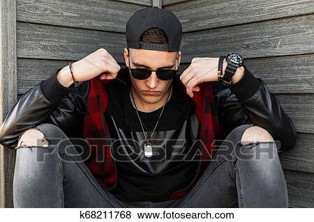 23cec8722bcc Joven, guapo, hipster, hombre, en, negro, gorra de béisbol, en, oscuridad,  gafas de sol, en, camiseta negra, en, moderno, chaqueta, en, vaqueros ...