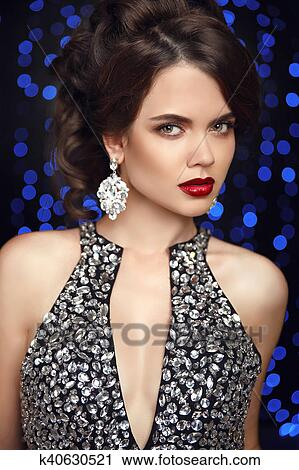 b8a9ee2628335 Beauty makeup. Fashion jewelry. Women portrait. Elegant lady with red lips,  hairstyle, diamond earrings posing isolated on studio dark blue party ...