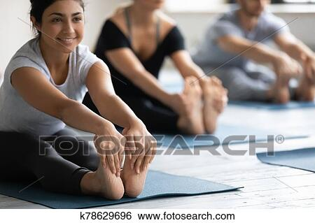 indian woman doing seated forward bend during yoga class