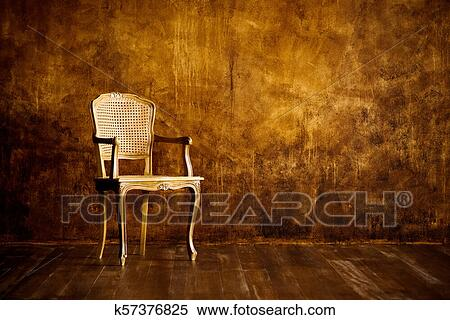 Old Chair On A Brown Wall Background