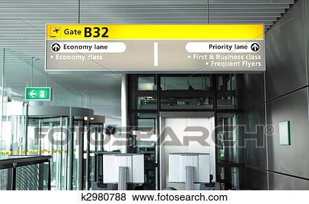 Departure Boarding Gate Inside A Modern Airport Terminal With Illuminated Head Sign Indicating Lanes For Class Of Passengers And Equipment Pass