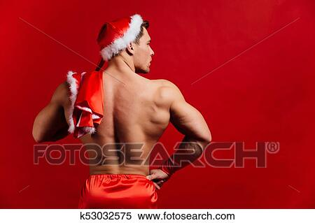 46875975f0509 Christmas holidays. sexy strong santa claus wearing hat. Young muscular man.  red background. Stock Photography