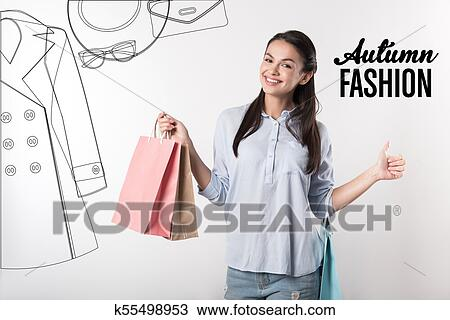 ff69911c09ac9 Fashion. Cheerful emotional young person feeling delighted while holding  convenient colorful paper bags and putting her thumb up after finishing  shopping