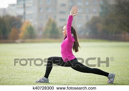 Sporty Beautiful Smiling Young Woman Practicing Yoga Standing In Warrior I Posture Virabhadrasana One Pose Working Out Outdoors On Summer Day Wearing