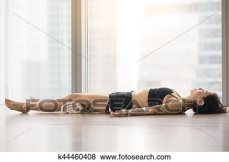 young attractive woman in savasana pose against floor