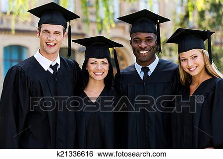 Stock Image - Ready to bright future. Four college graduates in graduation gowns standing close