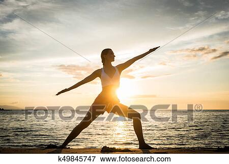 Full Length Side View Of The Silhouette A Fit Woman Practicing Warrior Yoga Pose Against Sky At Sunset During Summer Vacation In Flores Island