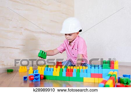 f63ae1bdcac Young boy wearing hardhat playing indoors sitting on a wooden floor  grinning as he holds up a large colorful plastic building block