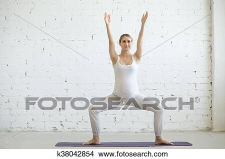pregnant young woman doing prenatal yoga sumo squat pose