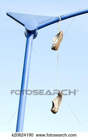 Old shoes hanging from their laces Stock Image