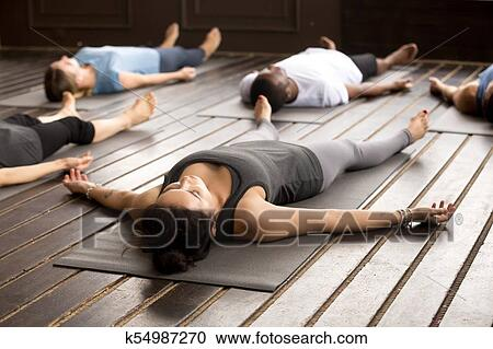 group of sporty people in savasana pose stock image