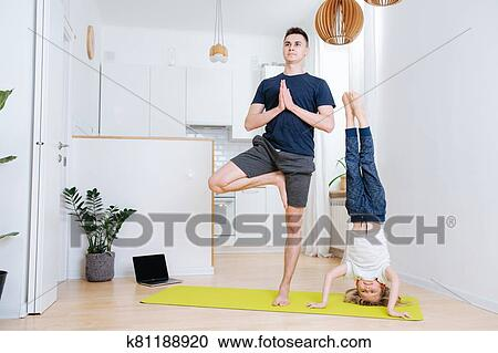 father and son doing yoga at home on a mat headstand and