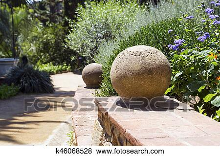 Part Of A Ladder With Stone Spheres In A Garden Stock Photo
