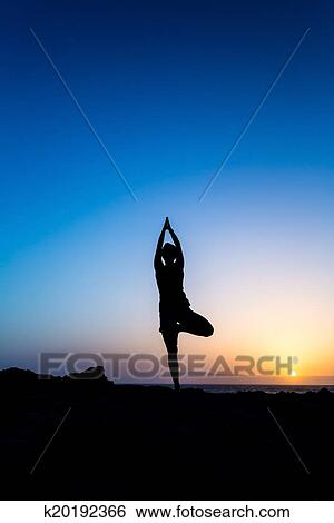 Young Woman Doing Beautiful Yoga Pose Tree Sunset Silhouette In Mountains Over Blue Sky And Clouds With Sun Sunlight Background
