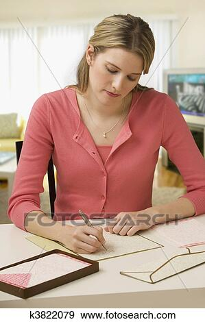 beautiful young woman concentrates while writing a letter at her desk vertical shot
