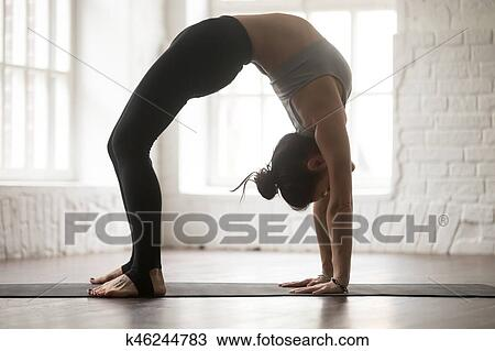 young attractive woman in urdhva dhanurasana pose white