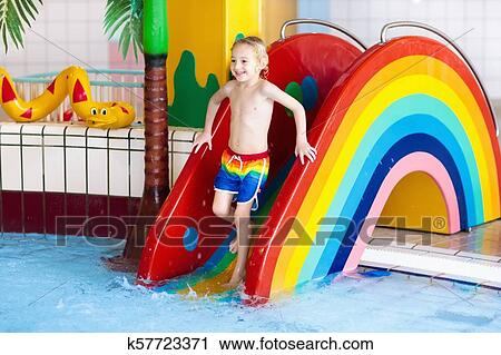 Child On Swimming Pool Slide Kid Having Fun Sliding In Water Amusement Park Kids Swim Family Summer Vacation Tropical Resort