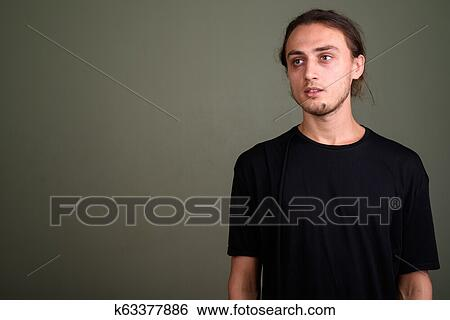 d4b814cef Stock Photograph - Young handsome man wearing black shirt against colored  backgroun. Fotosearch