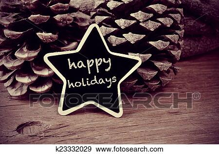 063d3146c518c The text happy holidays written in a star-shaped blackboard and some  pinecones on a rustic wooden table