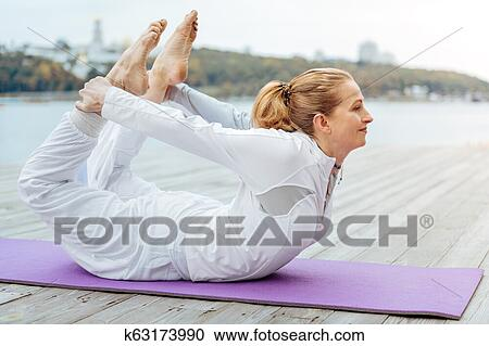 young woman laying in bow yoga pose stock image