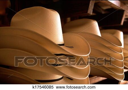 A stack of cream-colored straw Cowboy Hats with a thin brown leather band b85a4c252c2
