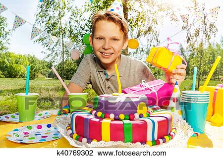 Portrait Of Happy Smiling Boy With Birthday Gifts Sitting Next To The Cake At Outdoor Party