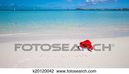 e221117669449 Santa Hat on white sandy beach and Merry Christmas written in the ...
