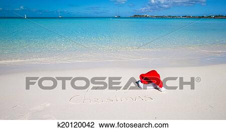 santa hat on white sandy beach and merry christmas written in sand - Merry Christmas Beach Images