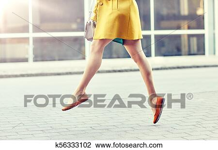 ca67ff836091 Fashion and people concept - happy young woman or teenage girl legs flying  above pavement on city street. k56333102 Foto search Stock ...