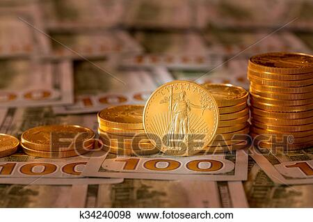 Picture Gold Coins Stacked On New Design 100 Dollar Bills Fotosearch Search Stock