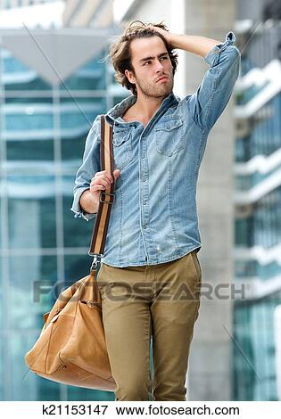 Picture Of Cool Guy Posing With Bag Outdoors K21153147