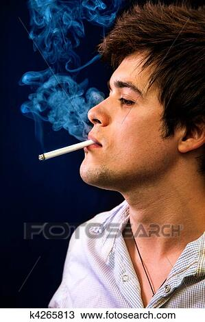 Stock Photo of Sexy cool young man smoking a cigar k4265813 ...