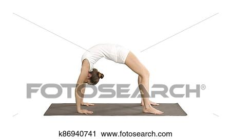 sporty yoga girl performing chakrasana urdva dhanurasana